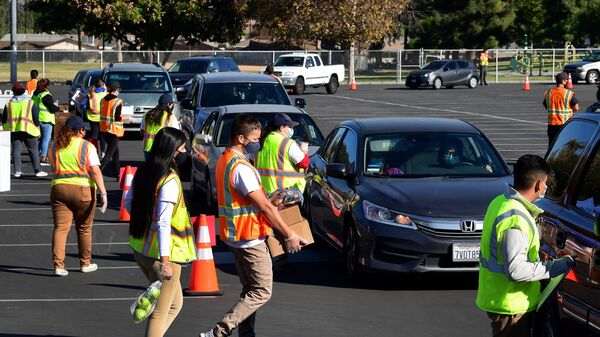 Food is loaded as drivers in their vehicles wait in line at a food distribution hosted by the Los Angeles Food Bank on Dec. 4 in Hacienda Heights, Calif.