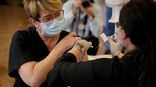A health care worker gets her COVID-19 vaccine at Rhode Island Hospital in Providence, RI on Monday.