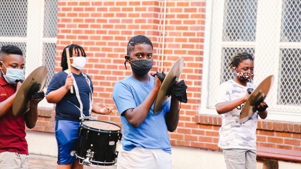 Students rehearse outdoors at The Roots of Music. The education nonprofit has kept its marching band going throughout the pandemic and resumed in-person rehearsal over the summer.
