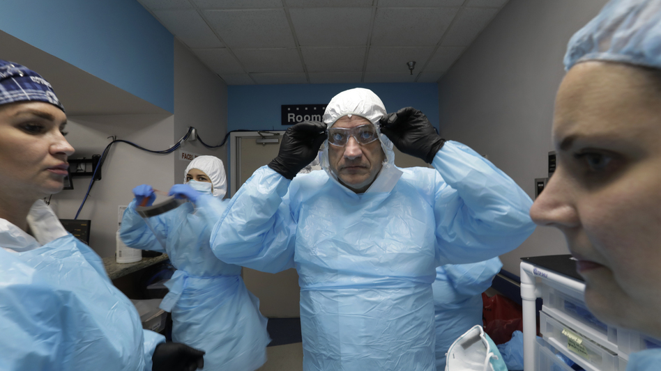 Dr. Joseph Varon prepares to enter the COVID-19 unit at Houston's United Memorial Medical Center in May. With him are nurses Tanna Ingraham (left) and Jerusha Harshman (right). (Carolyn Cole/Los Angeles Times via Getty Images)