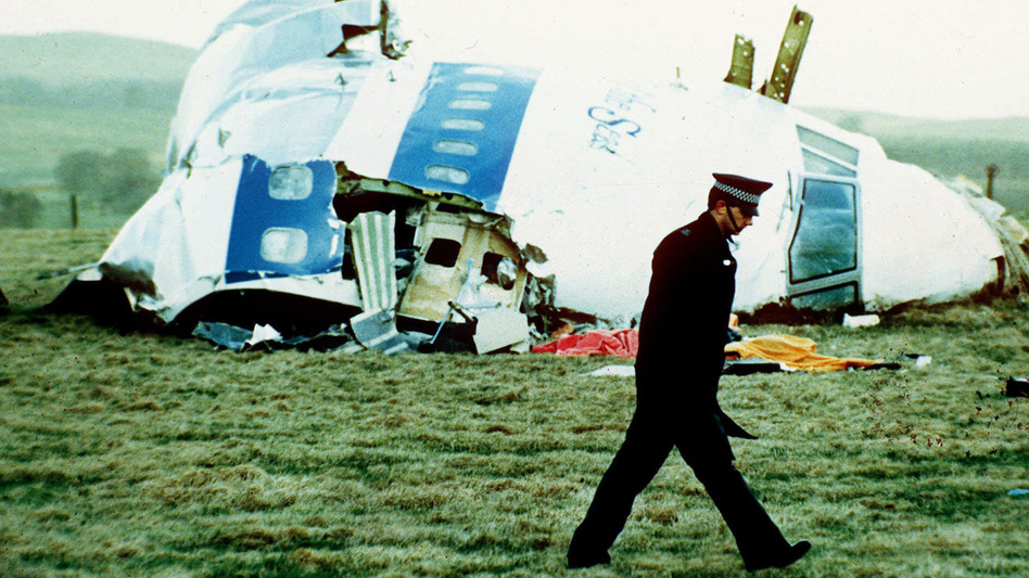 A police officer walks on Dec. 21, 1988, by the nose of Pan Am Flight 103 near Lockerbie, Scotland, where it lay after a bomb aboard exploded, killing a total of 270 people. (Martin Cleaver/AP)
