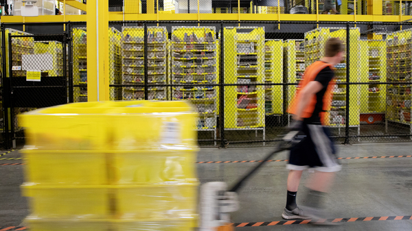 A worker pulls a pallet jack with plastic crates at an Amazon warehouse in New Jersey. The company is facing its biggest labor battle yet with a unionization vote expected at a facility in Alabama.