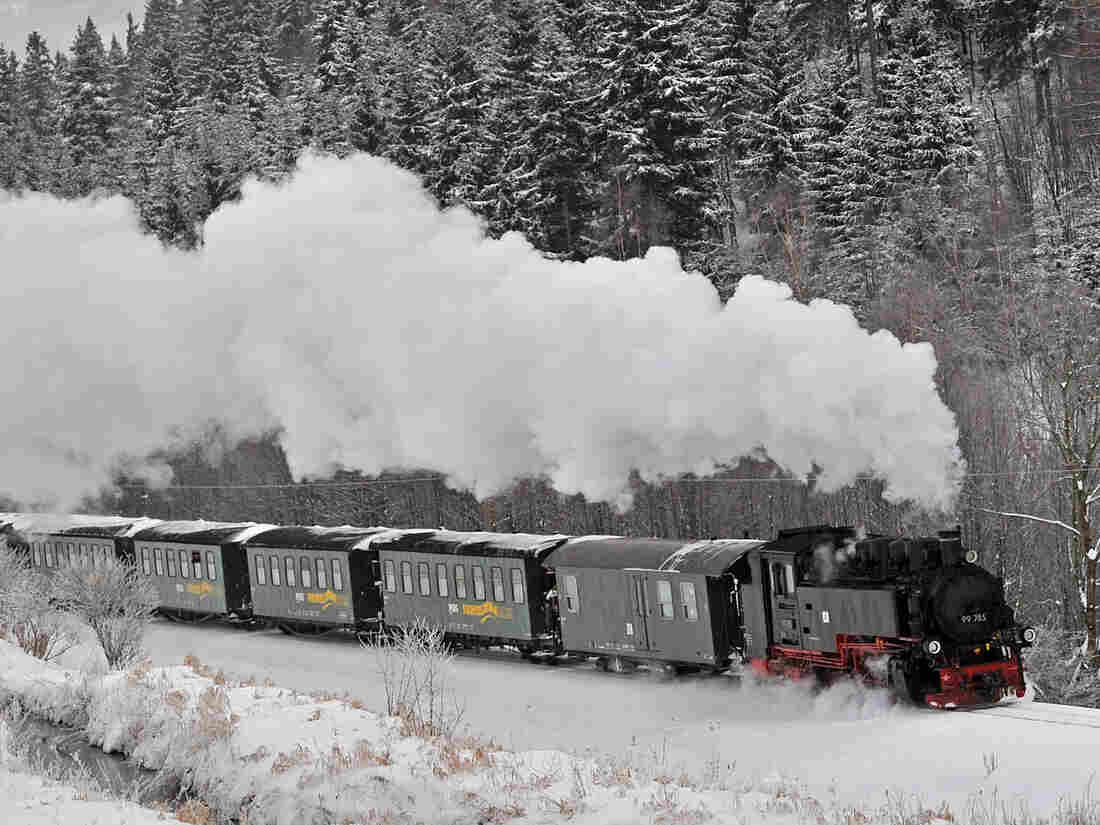 A steam engine makes its way through a snow-covered landscape.