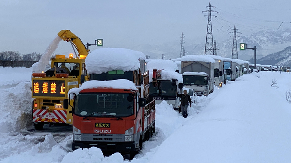 A snowplow clears a path beside cars stranded on the snow-covered Kan-etsu Expressway at the city of Minamiuonuma in Japan
