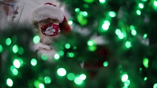 Bill Sandeen, dressed as Santa Claus, waits for the opening of a Santa drive-through selfie station in Las Vegas on Dec. 10. The real Santa was vaccinated by Dr. Anthony Fauci at the North Pole.
