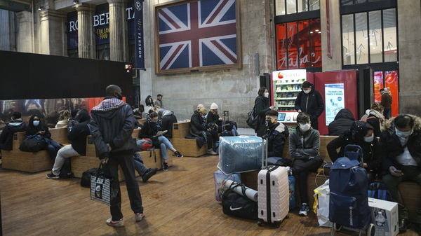 Passengers wearing face masks wait next to the Eurostar Terminal at Gare du Nord train station in Paris on Monday. France is banning all travel from the U.K. for 48 hours in an attempt to make sure that a new strain of the coronavirus in Britain doesn