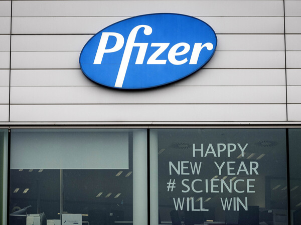 A sign is shown in the window of an office at Pfizer Manufacturing in Puurs, Belgium, on Monday, the same day the European Medicines Agency authorized the use of the company's coronavirus vaccine.