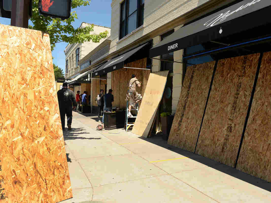 MINNEAPOLIS, MINNESOTA — Workers board up businesses up and down the 3700 block of Nicollet Ave. S., Saturday, May 30 2020. (Scott Takushi / MediaNews Group / St. Paul Pioneer Press via Getty Images)