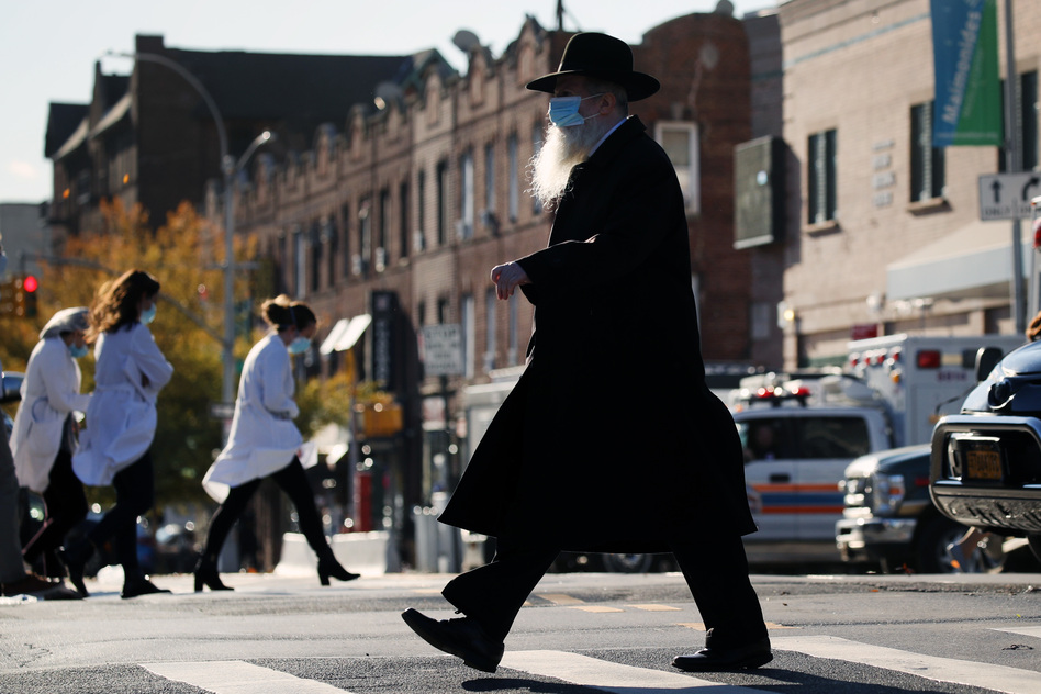 A Hasidic man and medical workers cross paths near the Maimonides Medical Center in Brooklyn, N.Y., in November. When public health messaging comes from community leaders, it's much more likely to be adopted, research on diverse groups finds. (Spencer Platt/Getty Images)