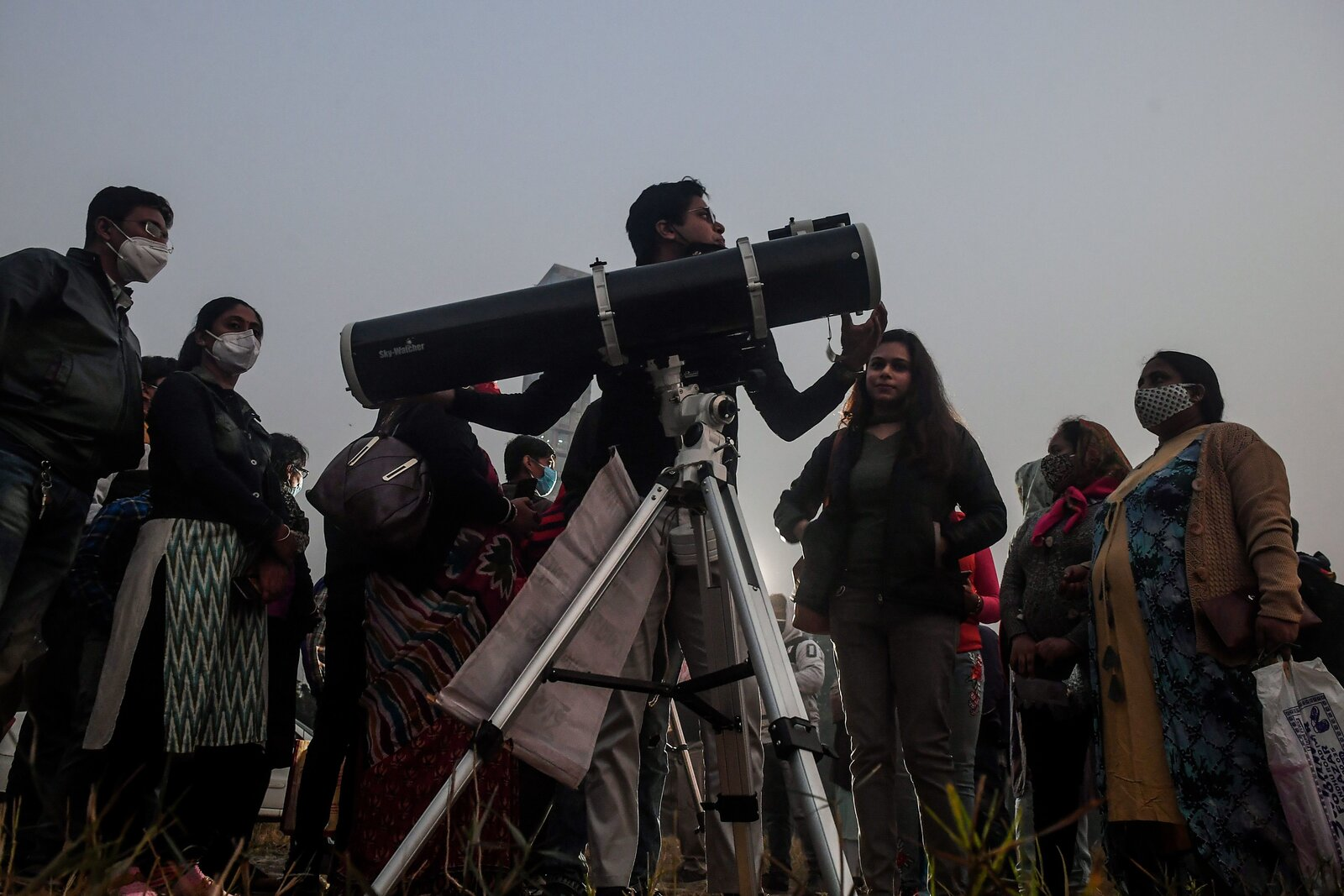 People stand in a queue to see the Great Conjunction at the Maidan area in Kolkata, India.
