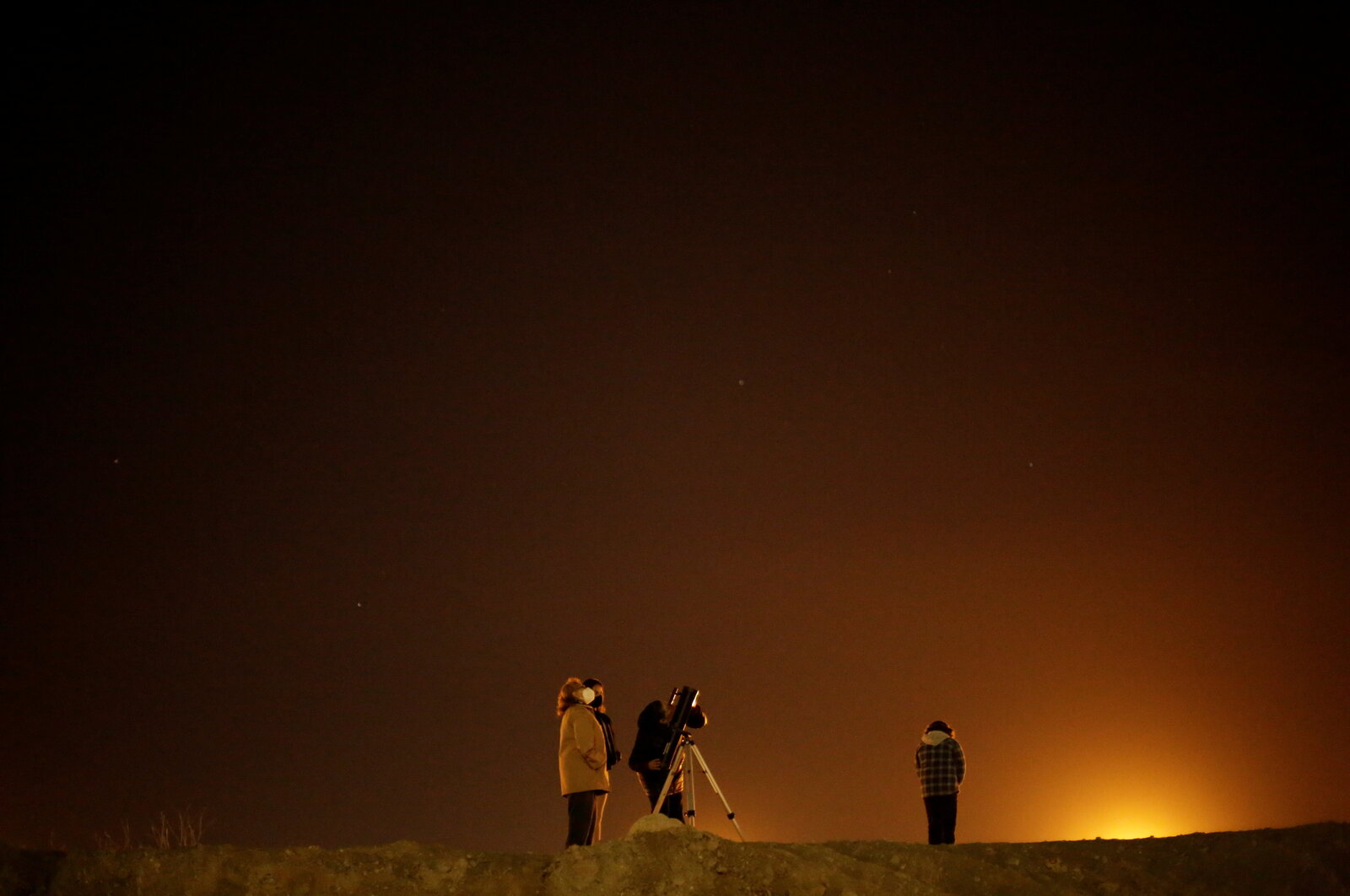 A family at the border crossing between Mexico and the U.S. in Ciudad Juarez uses a telescope to view Jupiter and Saturn during the Great Conjunction.