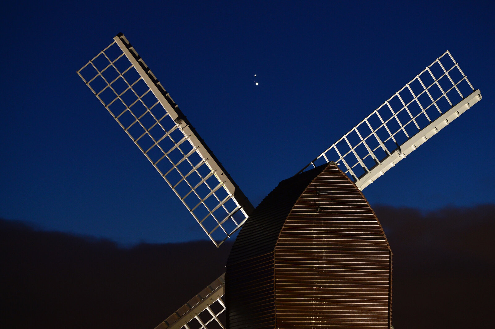 Jupiter and Saturn are seen coming together in the night sky, over the sails of Brill windmill in Brill, England.