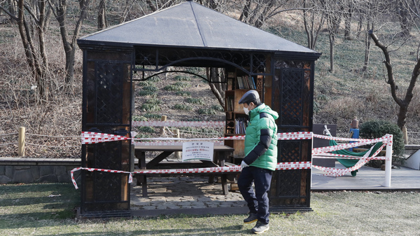 A man wearing a face mask walks past a rest area taped for social distancing as a precaution against the coronavirus in Seoul, South Korea, on Tuesday.