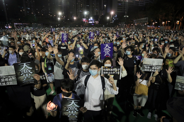 """After Hong Kong's huge pro-democracy demonstrations in 2019, the Chinese government imposed a new security law this year. Still, protests continued. At a June 4 vigil for victims of the 1989 Tiananmen Square massacre, demonstrators gesture with five fingers, signifying """"five demands — not one less,"""" and hold posters reading """"Heaven will destroy the CCP,"""" referring to the Chinese Communist Party."""