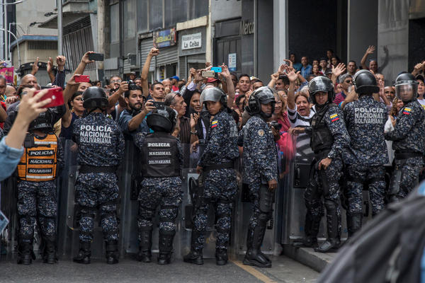 Juan Guaidó, accompanied by legislators of the opposition parties, fights a military blockade to the National Assembly in January in Caracas. Guaidó and opposition legislators were prevented from joining the sessions.
