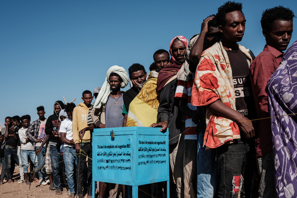 Newly arrived Ethiopian refugees who fled the Tigray conflict wait to receive aid at Um Raquba refugee camp in Gedaref, eastern Sudan, on Dec. 6.