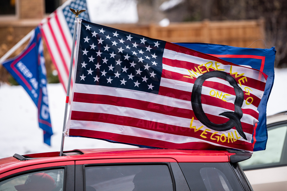 A car with a flag endorsing the QAnon conspiracy theory drives by as supporters of President Trump gather for a rally outside the Governor's Residence in St. Paul, Minn., on Nov. 14. (Stephen Maturen/Getty Images)
