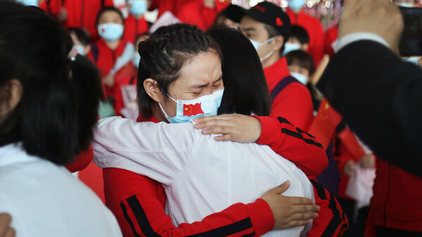 Health workers from Tongji Hospital in Wuhan, China, share an emotional embrace with their peers from a hospital in Jilin province at the Tianhe Airport. Colleagues who worked on the front lines together bid farewell as Wuhan lifted its coronavirus lockdown in April.