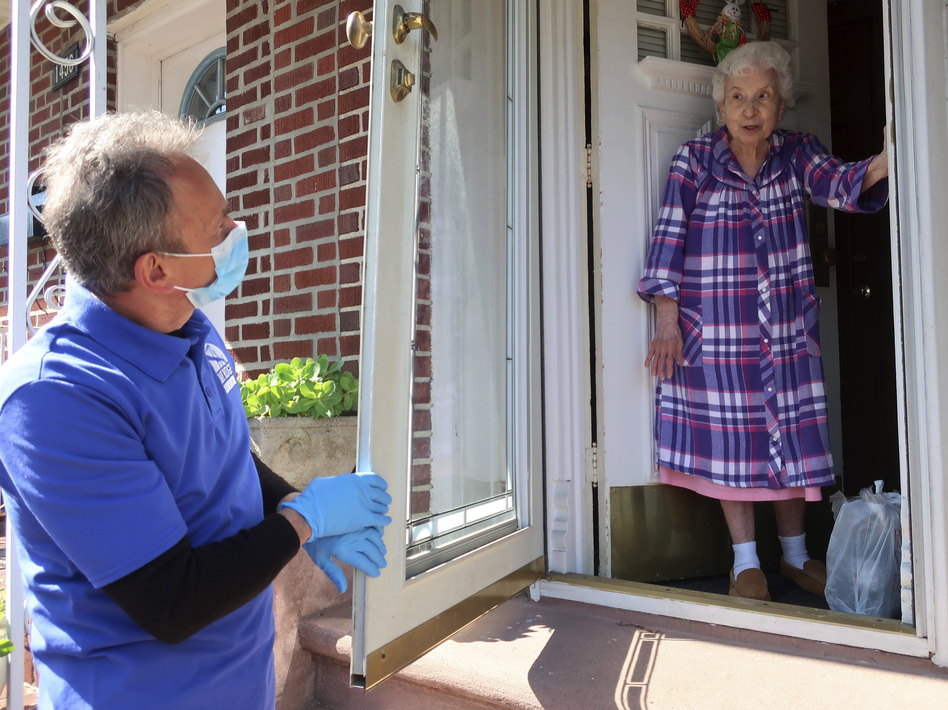 Homebound senior Louise Delija, 93, receives a meal delivery in Brooklyn, New York. Since the pandemic began, demand for help from seniors has ballooned. (Ted Shaffrey/AP)