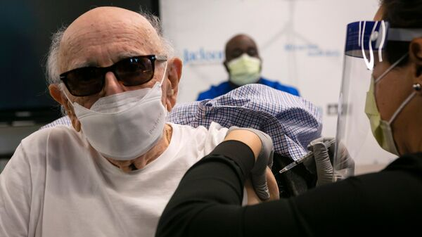 Norman Einspruch, 88, a cardiology patient at Jackson Memorial Hospital in Miami, Fla., receives his first dose of the Pfizer-BioNtech COVID-19 vaccine Dec. 30.