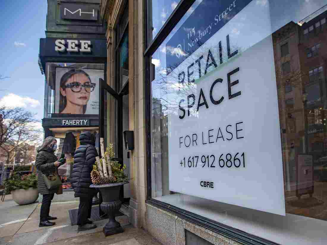 Two women walk into a store next to a vacant retail spot for lease on Newbury Street. (Jesse Costa/WBUR)