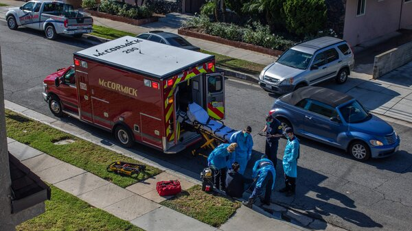 Los Angeles County paramedics examine a potential COVID-19 patient sitting on a curb before transporting him to a hospital in Hawthorne, Calif., on Dec. 29.