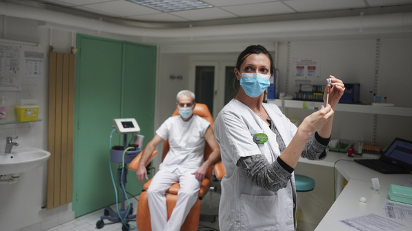 A nurse prepares to administer the Pfizer-BioNTech COVID-19 vaccine to Dr. Jean-Christophe Richard in La Croix-Rousse hospital, in Lyon, France, on Wednesday. Amid public outcry, France