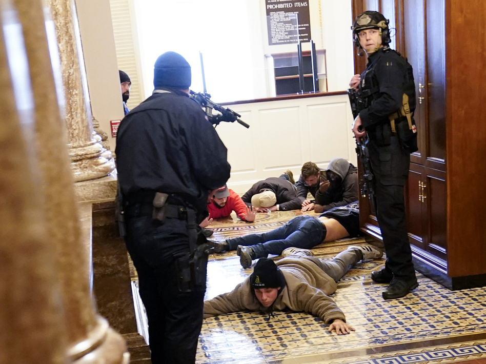 U.S. Capitol Police hold protesters at gunpoint near the House Chamber inside the U.S. Capitol on Wednesday. (Andrew Harnik/AP)