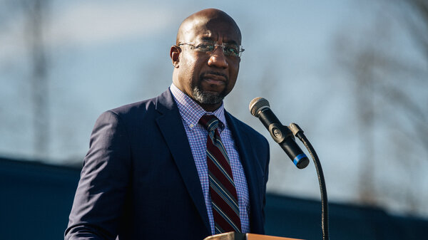 The Rev. Raphael Warnock, a Democrat, speaks at a drive-in rally on Monday in Riverdale, Ga.