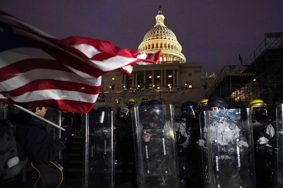Police stand behind their shields outside the Capitol after a day of rioting on Wednesday. (Julio Cortez/AP)