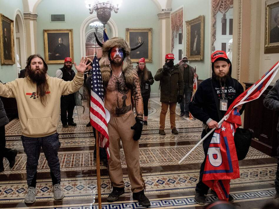Supporters of President Trump, including Jake Angeli (center), a QAnon supporter known for his painted face and horned hat, stand inside the U.S. Capitol on Jan. 6. Demonstrators breached security and entered the Capitol as Congress was in the process of tallying the 2020 electoral vote count. (Saul Loeb/AFP via Getty Images)