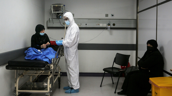 Inside an emergency room at Rafik Hariri Hospital on Nov. 17, a medic wearing full protective gear checks a woman who might have the coronavirus. Beirut hospitals are reaching maximum capacity amid an influx of coronavirus patients.