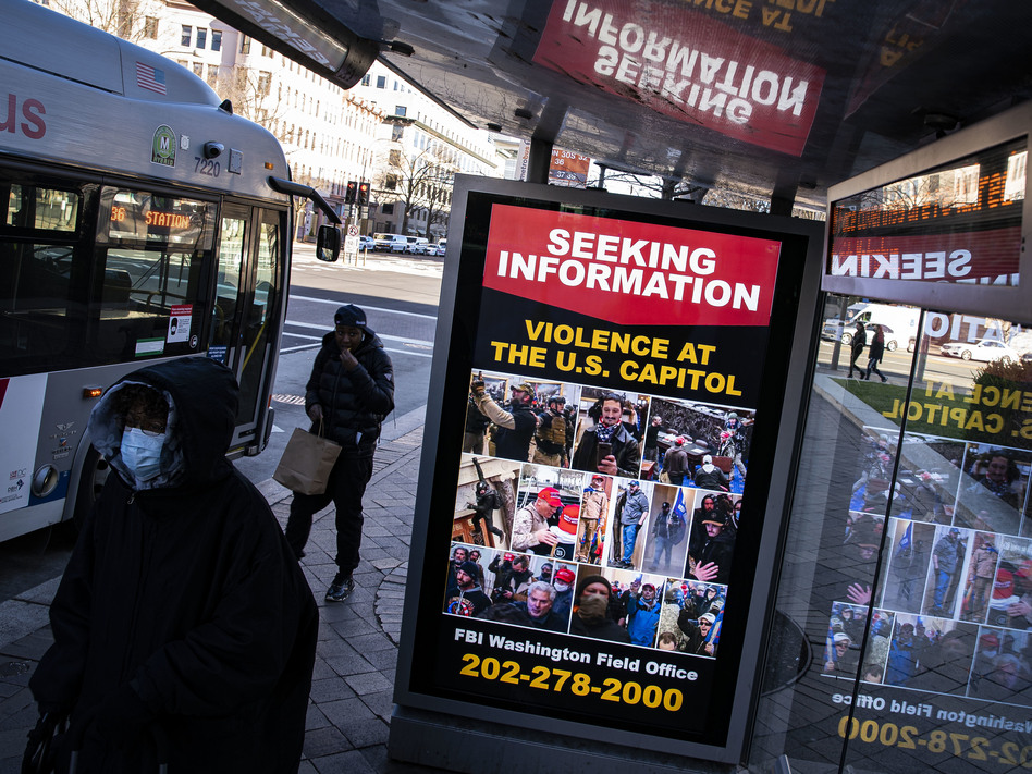 At a bus stop on Pennsylvania Avenue Northwest in Washington, D.C., a notice from the FBI seeks information about people pictured during the riot at the U.S. Capitol on Wednesday. (Al Drago/Getty Images)