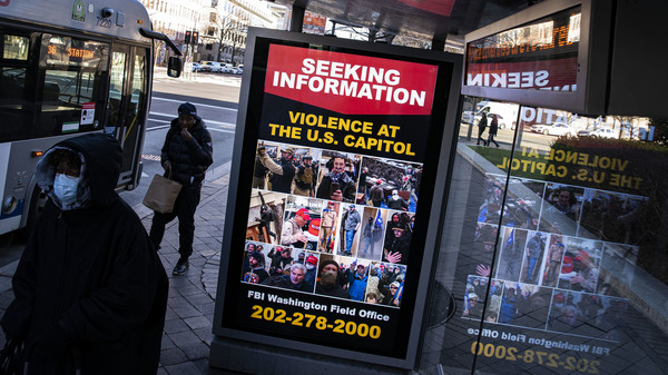 A billboard on a bus stop on Pennsylvania Ave. NW in Washington, D.C., advertises a message from the Federal Bureau of Investigation seeking information related to violence at the U.S. Capitol on Wednesday.