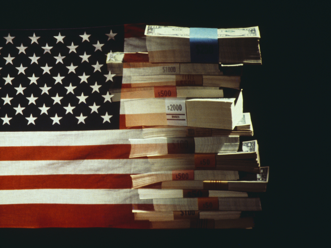 The American flag superimposed over a pile of U.S. dollar bank notes.