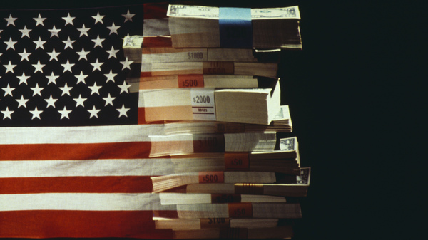 The American flag superimposed over a pile of U.S. dollar banknotes.