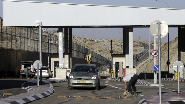 "A checkpoint is seen on a West Bank highway near Jerusalem  which critics have branded an ""apartheid highway."" The highway features a large concrete wall segregating Israeli and Palestinian traffic."