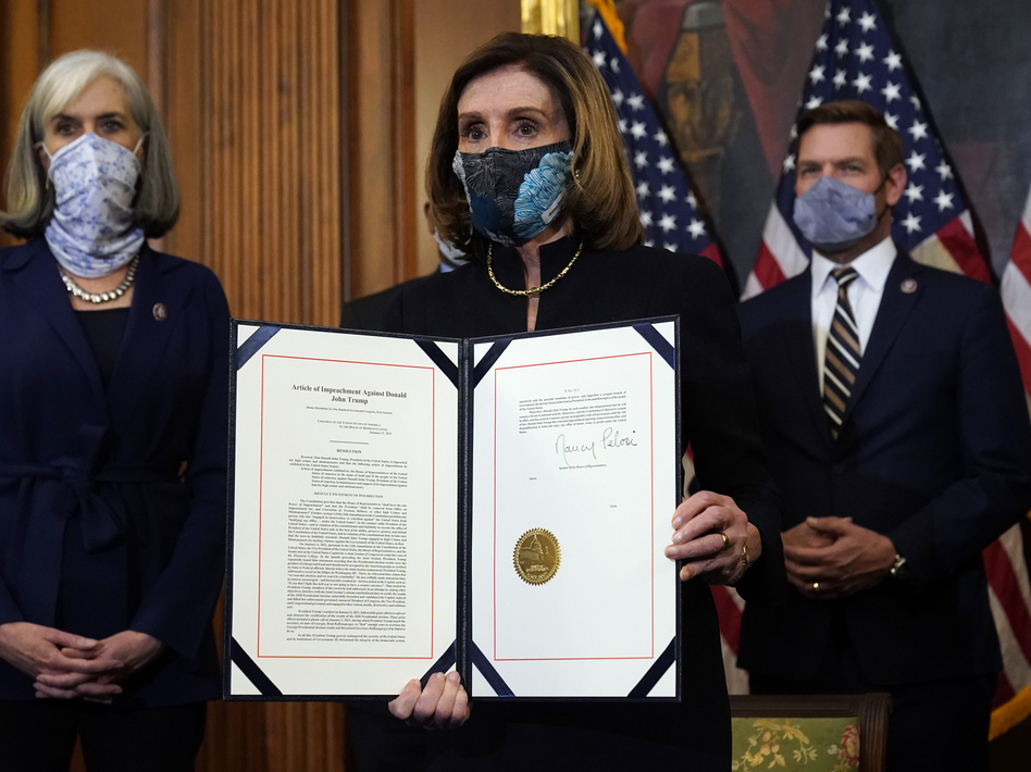House Speaker Nancy Pelosi of California displays the signed article of impeachment against President Trump in an engrossment ceremony before transmission to the Senate for trial on Capitol Hill. It's unclear when a Senate trial will start. (Alex Brandon/AP)