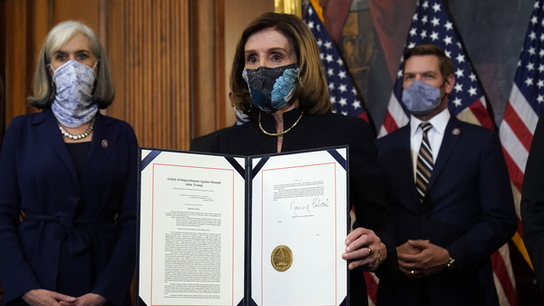 House Speaker Nancy Pelosi of Calif., displays the signed article of impeachment against President Donald Trump in an engrossment ceremony before transmission to the Senate for trial on Capitol Hill. It