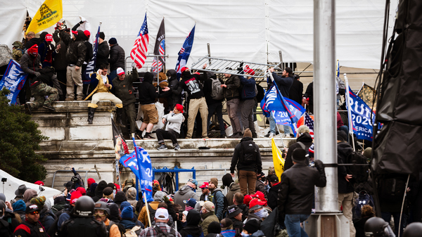 A group of pro-Trump protesters climb the walls of the U.S. Capitol after storming the west lawn on Jan. 6. A pro-Trump mob broke windows in the Capitol and clashed with police officers. Now there is debate whether federal charges of seditious conspiracy should be used against them.