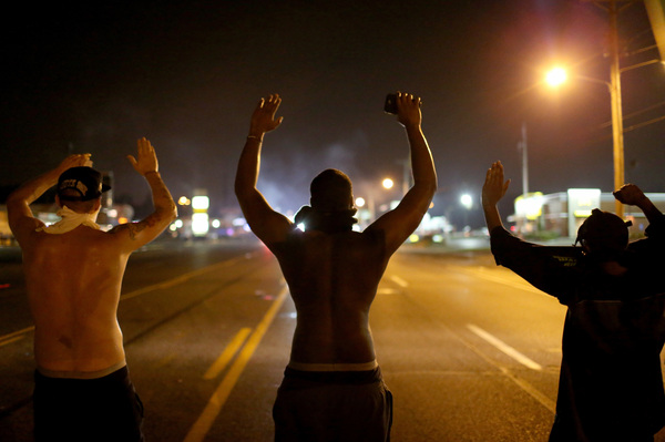 "Demonstrators raise their arms and chant, ""Hands up, don't shoot"" on Aug. 17, 2014, as they protest the shooting death of Michael Brown in Ferguson, Mo."