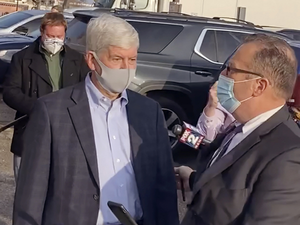 In this image taken from video, former Michigan Gov. Rick Snyder, left, with his lawyer, Brian Lennon, leave Genesee County Court in Flint, Mich., after a initial court appearance via Zoom on two misdemeanor counts of willful neglect of duty in connection to the Flint water crisis.