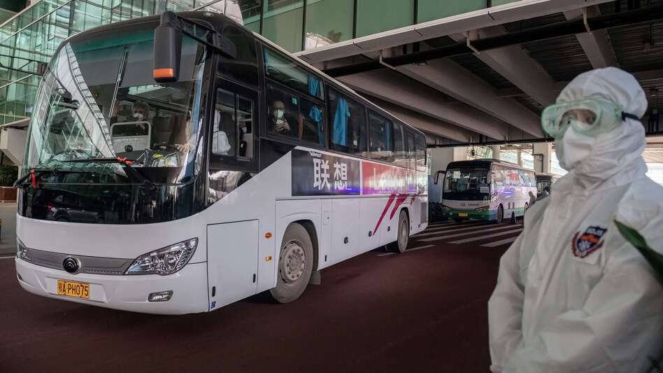 A bus carrying members of the World Health Organization team investigating the origins of the COVID-19 pandemic leaves Wuhan's airport following their arrival at a cordoned-off section in the international arrivals area on Thursday.