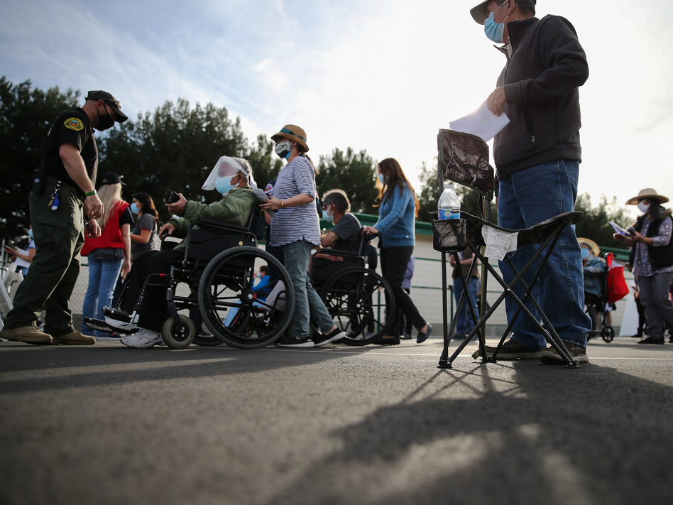 People lined up to receive the COVID-19 vaccine at a mass vaccination site in Disneyland's parking lot in Anaheim, Calif. on Jan. 13. The state says all residents 65 or older are now eligible to receive the vaccine. (Mario Tama/Getty Images)