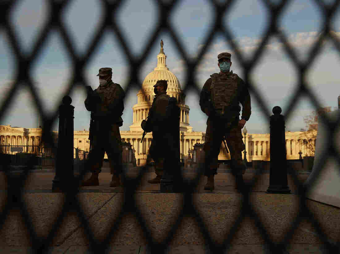 Members of the New York National Guard stand guard along the fence that surrounds the U.S. Capitol in Washington, D.C., on Jan. 14, the day after the House of Representatives voted to impeach President Trump for the second time.