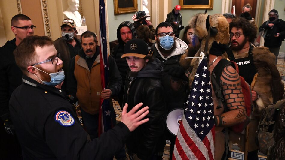 """Jacob Chansley, the """"QAnon Shaman"""" known for his painted face and horned hat, was taken into custody in Arizona in connection with the assault on the U.S. Capitol on Jan 6. (Saul Loeb/AFP via Getty Images)"""