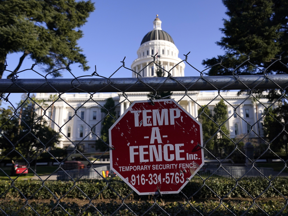 """A temporary 6-foot-high chain-link fence now surrounds California's state Capitol. Gov. Gavin Newsom said Thursday, """"Let me be clear: There will be no tolerance for violence."""" (Rich Pedroncelli/AP)"""