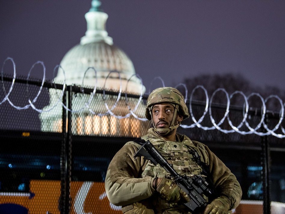 A member of the Virginia National Guard stands outside the razor wire fencing surrounding the U.S. Capitol on Friday. Up to 25,000 troops are expected by Inauguration Day. (Liz Lynch/Getty Images)