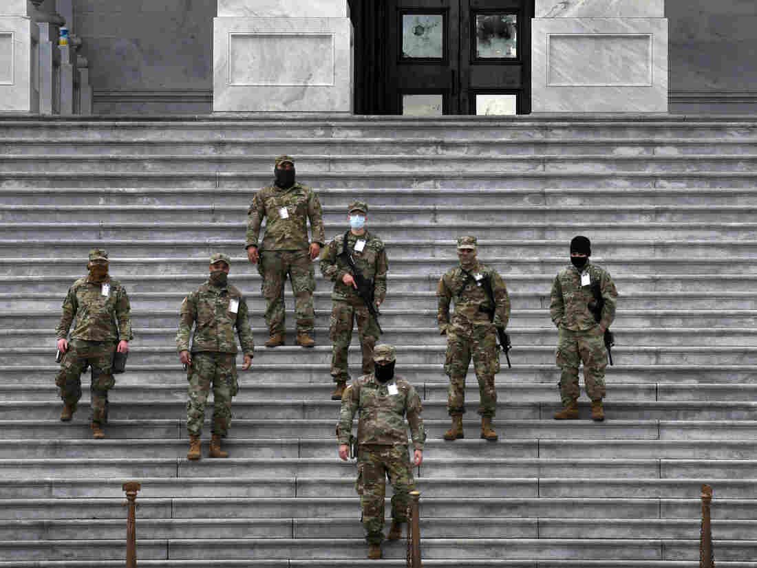 National Guard troops provide security at the U.S. Capitol for the upcoming inauguration for President-elect Joe Biden amid threats by extremist supporters of Donald Trump in Washington DC on January 17, 2021. There were threats to storm capitols in all 50 states but the day remained quiet. Shattered windows behind them.