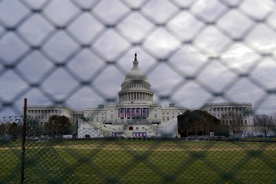 The U.S. Capitol is visible behind fences on Sunday following the Jan. 6 riot by pro-Trump extremists. This week's events will have the largest security presence of any inauguration in U.S. history. (Eric Thayer/Getty Images)